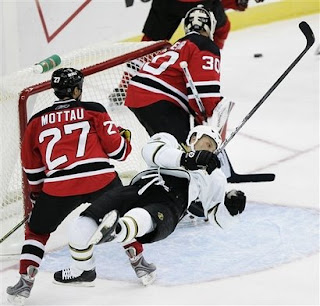 Dallas Stars' Sean Avery gets knocked down by New Jersey Devils' Mike Mottau (27) as Devils goalie Martin Brodeur (30) watches the puck dyring the third period of an NHL hockey game in Newark, N.J., Wednesday, Oct. 22, 2008. The Devils defeated the Stars 5-0.