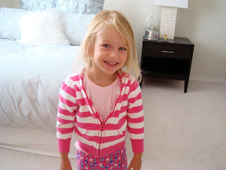 Young girl wearing pink smiling standing in bedroom