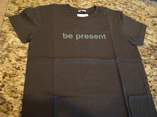 Grey t-shirt with the phrase be present