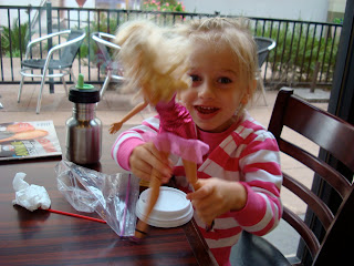 Young girl playing with Barbie at table