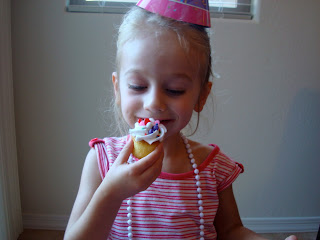Young girl wearing birthday hate eating cupcake