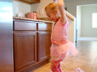 Young girl dancing in kitchen wearing tutu