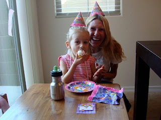 Young girl eating cupcake with woman behind her smiling