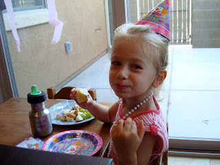 Young girl in birthday hat smiling and eating