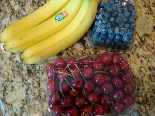 Cherries, bananas and blueberries on countertop