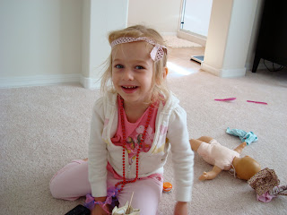 Young girl playing dress up on floor with toys