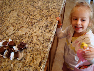 Young girl holding doll looking at candy on countertop