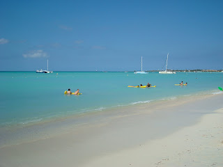 Beach in Aruba with boats and people in water