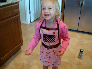 Young girl wearing apron in kitchen