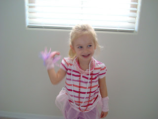 Young girl in bedroom waving while wearing dress up clothes
