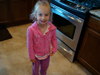 Young girl in pink standing in kitchen