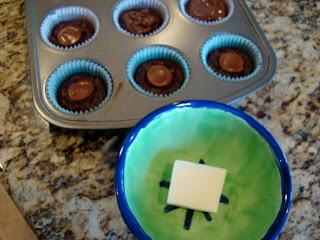 Piece of white chocolate in bowl next to cupcake pan