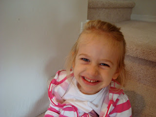 Young girl smiling for camera on steps