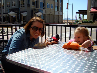 Woman and young girl sitting at outdoor table at coffee shop