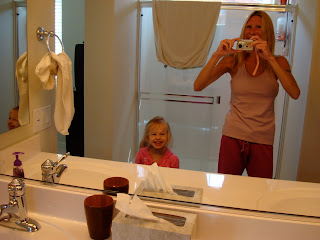 Young girl and woman smiling into mirror in bathroom