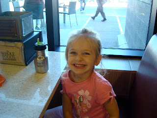 Little girl sitting in booth smiling