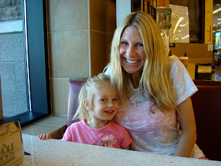 Woman and young girl sitting in booth smiling