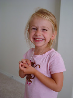 Young girl smiling and holding necklace around neck