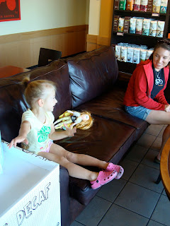 Young girl with dolls sitting next to woman on couch