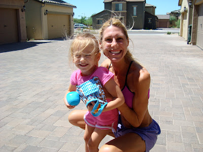 Woman hugging young girl from behind while playing catch