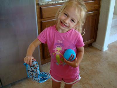 Young girl holding baseball glove and ball