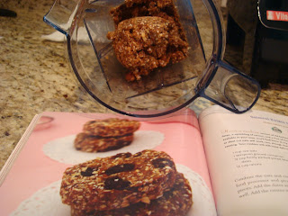 Open cookbook with oatmeal raisin cookie mixture in blender