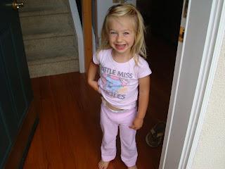 Little girl smiling in her pajamas in doorway
