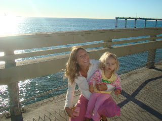 Woman and young girl smiling on pier with ocean in background