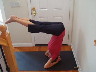 Woman doing half headstand yoga pose