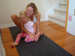 Woman and little girl sitting on yoga mat hugging and smiling