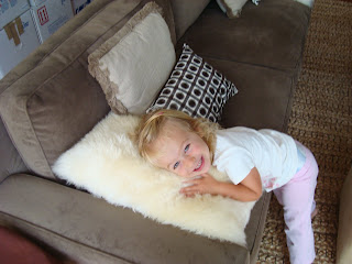 Smiling little girl cuddling fuzzy pillow on brown couch