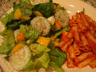 Mixed veggie salad with size of ziti and marinara on white plate