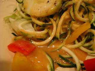Spiralized zucchini on plate showing pooling of peanut sauce