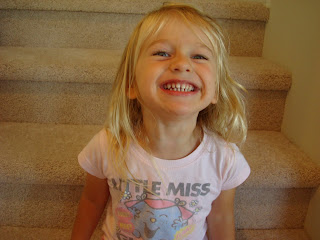 Photo of young girl giving big smile in front of staircase