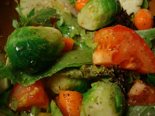 Greens topped with Brussel sprouts and tomatoes tossed in dressing