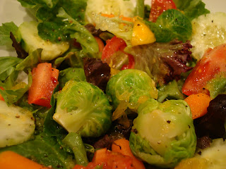 Close up of mixed greens topped with vegetables and dressing in white bowl