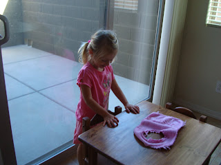 Young girl in pink playing at child's sized table