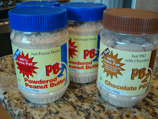 Three containers of Peanut Butter Powder one being Chocolate