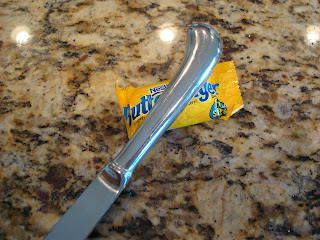 End of butter knife crushing up a mini sized butterfinger candy bar