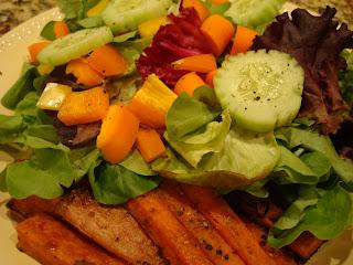 Simple vegetable salad served alongside sweet potato fries
