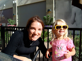 Woman with arm around young girl smiling wearing large yellow sun glasses