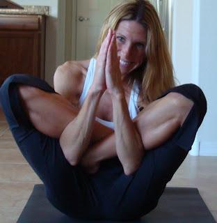 Woman doing Garbha Pindasana yoga pose