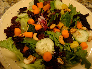 Salad with mixed greens, cashews, vegetables and dulse flakes in shallow white dish