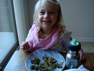 Young girl sitting at table eating plate of Kale Chips