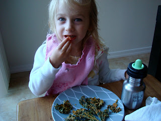 Young girl putting one Kale Chip in mouth