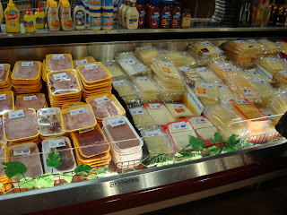 Deli meats and cheese's in refrigerator section of grocery store