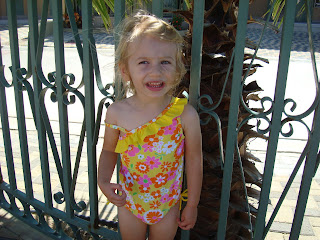 Young girl standing by fence in swimsuit