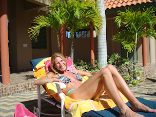 Woman on towel lined lounge chair in bathing suit