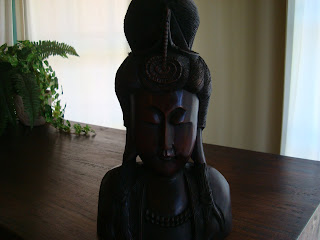 Dark chocolate-colored wooden statue on table