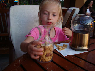 Young girl eating a jar of mixed nuts